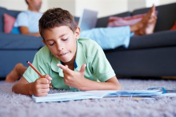 Young boy lying on the floor studying, using fingers to count