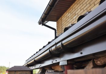 Holder gutter drainage system on the roof. Closeup of problem areas for plastic rain gutter waterproofing.